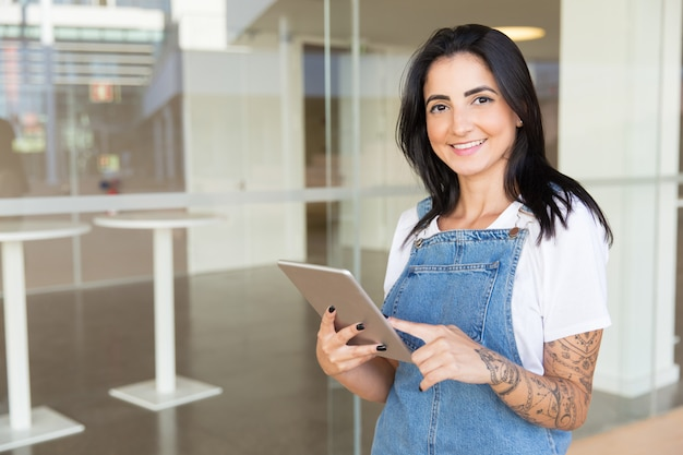 Zadowolona młoda kobieta trzyma cyfrową pastylkę