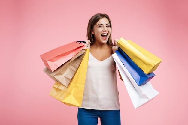 Zadowolona młoda kobieta trzyma torby na zakupy i wygląda bardzo szczęśliwy