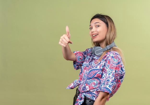 Zadowolona młoda kobieta ubrana w koszulę z nadrukiem paisley w słuchawkach pokazująca kciuk do góry