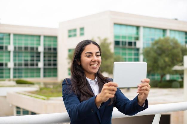 Zadowolona młoda kobieta używa pastylka komputer osobistego