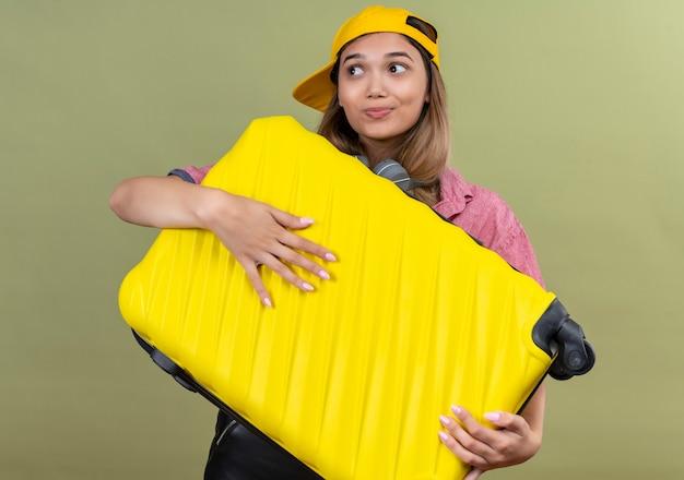 Zadowolona młoda kobieta w czerwonej koszuli i żółtej czapce baseballowej ze słuchawkami, niosąca żółtą walizkę na zielonej ścianie