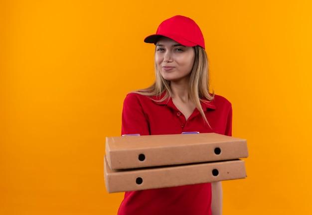 Zadowolona młoda kobieta w czerwonym mundurze i czapce trzyma pudełko po pizzy