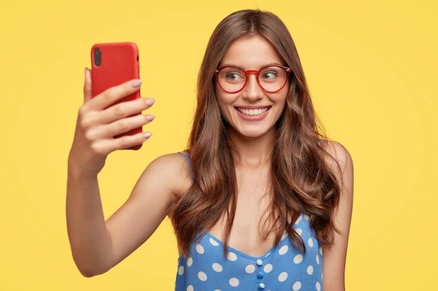 Zadowolona młoda kobieta w okularach pozuje na żółtej ścianie