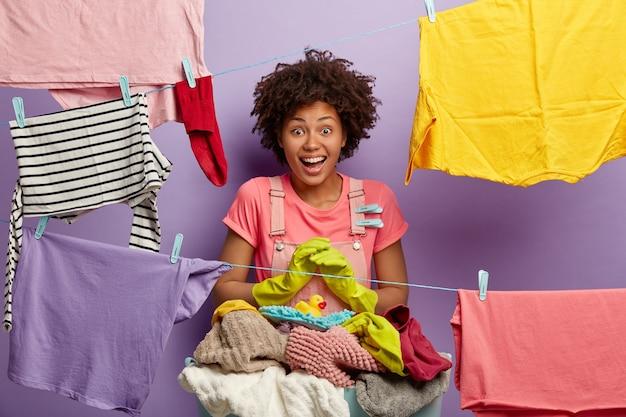 Zadowolona młoda kobieta z afro pozuje z praniem w kombinezonie