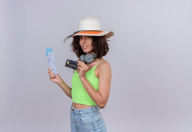 Zadowolona młoda kobieta z krótkimi włosami w zielonej bluzce na sobie kapelusz przeciwsłoneczny, trzymając bilety lotnicze i kartę kredytową na białym tle