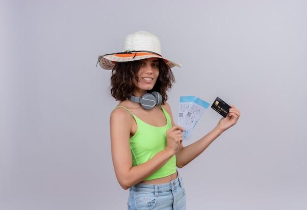 Zadowolona młoda kobieta z krótkimi włosami w zielonej bluzce, w kapeluszu przeciwsłonecznym, pokazująca bilety lotnicze i kartę kredytową na białym tle