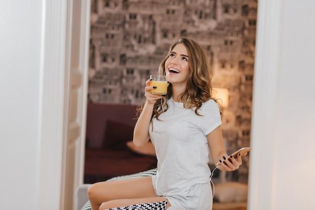Zadowolona młoda kobieta z lśniącymi kręconymi włosami pije rano sok pomarańczowy