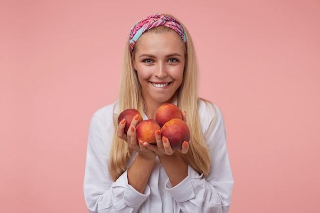 Zadowolona młoda kobieta z pomarańczowym manicure i brzoskwiniami w dłoniach, wyglądająca i gryząca dolną wargę, niecierpliwie czekająca na jej zjedzenie, odizolowana