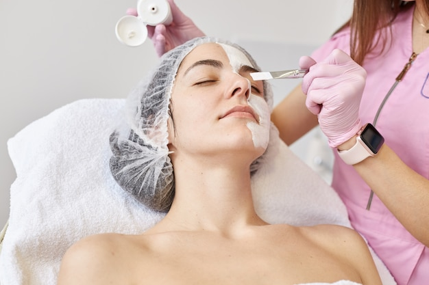 Zadowolona młoda kobieta z zamkniętymi oczami, relaksująca się na trenerze kosmetycznym, mająca medyczną czapkę na głowie, spędzająca czas w salonie piękności, pozuje nad białą ścianą, jest naga w ręczniku.
