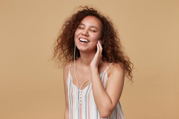 Zadowolona młoda, kręcona brunetka dama z naturalnym makijażem, trzymająca podniesioną rękę na słuchawce i uśmiechająca się radośnie z zamkniętymi oczami, pozująca na beżu