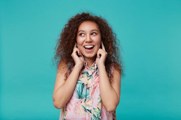 Zadowolona młoda, kręcona brunetka kobieta z naturalnym makijażem trzymająca palce wskazujące na uszach podczas słuchania muzyki w słuchawkach, odizolowana na niebiesko