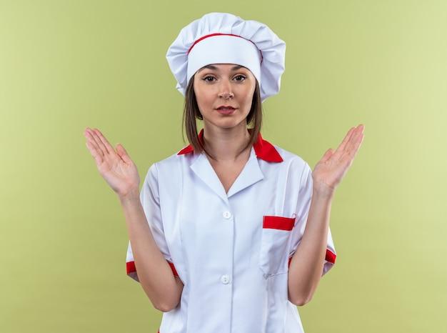 Zadowolona młoda kucharka ubrana w mundur szefa kuchni pokazujący rozmiar na oliwkowozielonej ścianie!