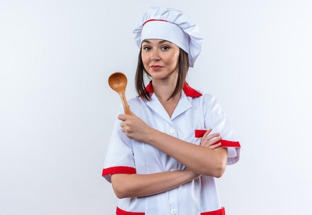 Zadowolona młoda kucharka ubrana w mundur szefa kuchni trzymająca łyżkę krzyżującą ręce odizolowane na białej ścianie