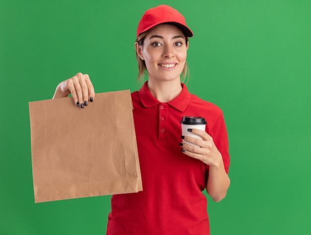Zadowolona młoda ładna dziewczyna dostawy w mundurze trzyma papierowy pakiet i papierowy kubek na zielono