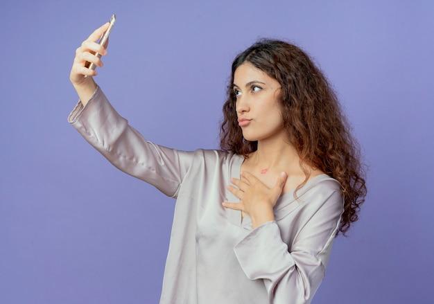 Zadowolona młoda ładna dziewczyna robi selfie i kładzie rękę na piersi na białym tle na niebieskiej ścianie