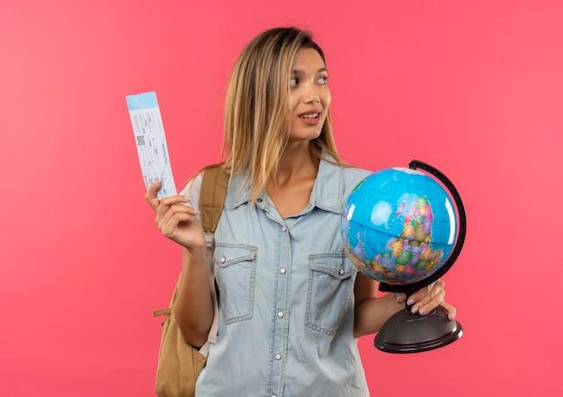 Zadowolona młoda ładna dziewczyna studentka na sobie tylną torbę, trzymając bilet lotniczy i kula ziemska, patrząc z boku na białym tle na różowej ścianie