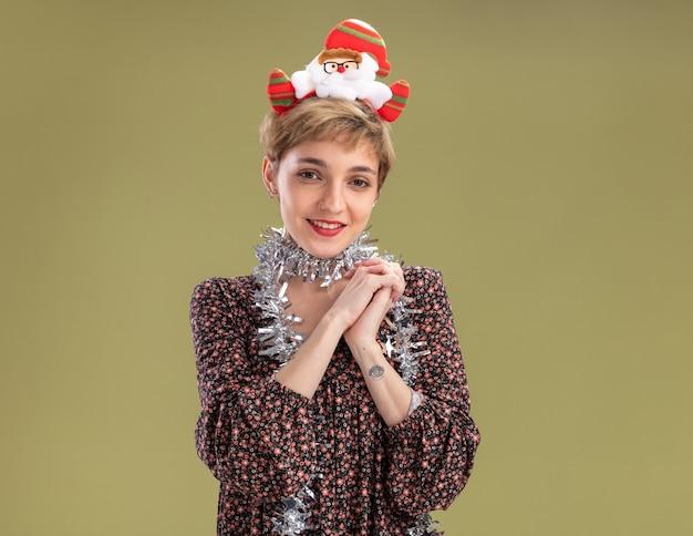 Zadowolona młoda ładna dziewczyna ubrana w opaskę świętego mikołaja i blichtrową girlandę na szyi trzymającą ręce razem odizolowaną na oliwkowozielonej ścianie z kopią przestrzeni