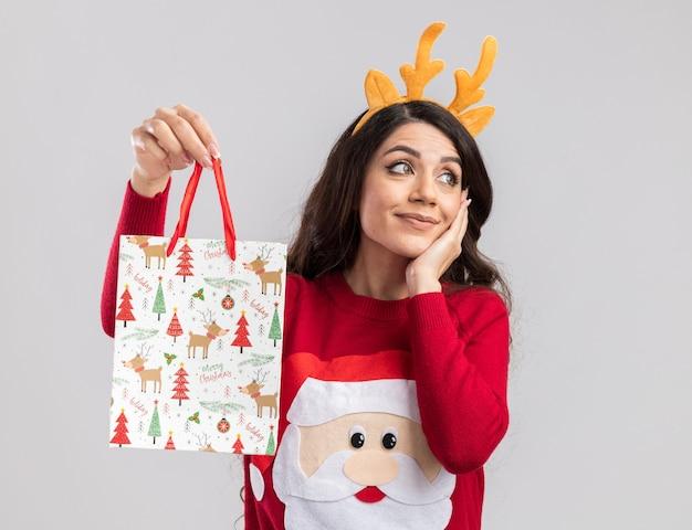 Zadowolona młoda ładna dziewczyna ubrana w opaskę z poroża renifera i sweter świętego mikołaja trzyma torbę z prezentami świątecznymi, trzymając dłoń na twarzy, patrząc z boku