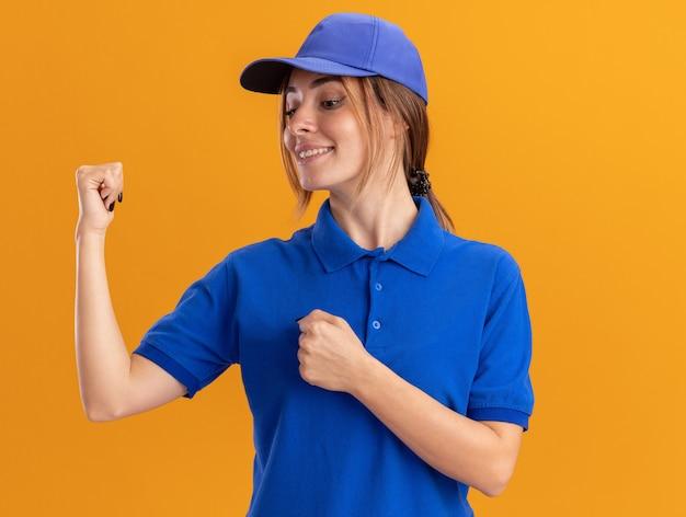 Zadowolona młoda ładna dziewczyna w mundurze dostawy trzyma pięści i spogląda z góry na pomarańczę