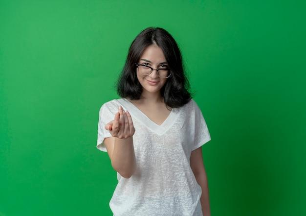 Zadowolona młoda ładna dziewczynka kaukaski w okularach robi tu gest na białym tle na zielonym tle z miejsca na kopię