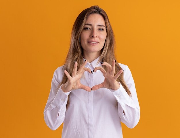 Zadowolona młoda ładna kaukaska dziewczyna gestykuluje znak serca na pomarańczowej ścianie z kopią miejsca
