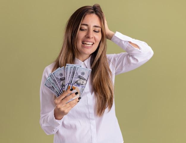 Zadowolona młoda ładna kaukaska dziewczyna kładzie rękę na głowie, trzymając i patrząc na pieniądze