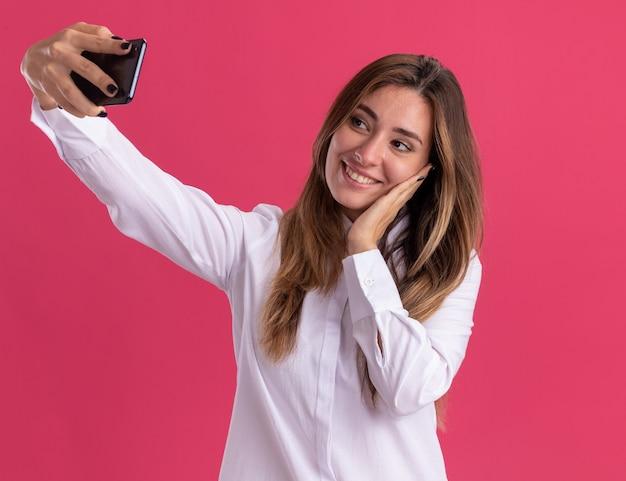 Zadowolona młoda ładna kaukaska dziewczyna kładzie rękę na twarzy, trzymając i patrząc na telefon, biorąc selfie