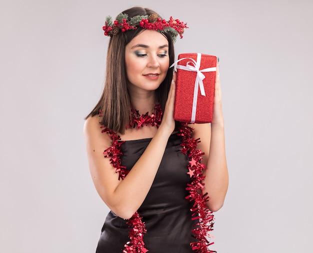 Zadowolona młoda ładna kaukaska dziewczyna nosi świąteczny wieniec z głowy i blichtrową girlandę wokół szyi, trzymając i patrząc na pakiet prezentów na białym tle z miejsca kopiowania