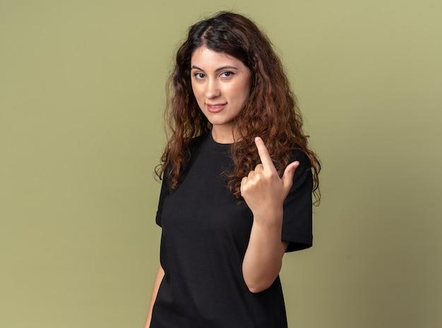 Zadowolona młoda ładna kaukaska dziewczyna stojąca w widoku profilu, robiąca gest chodź tutaj na oliwkowo-zielonej ścianie z miejscem na kopię