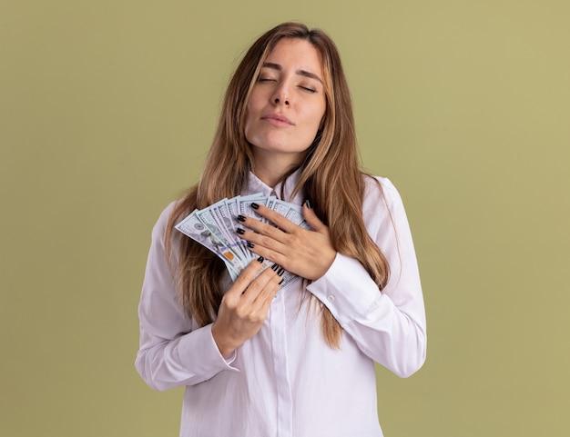 Zadowolona młoda ładna kaukaska dziewczyna trzyma pieniądze na piersi na oliwkowozielonej ścianie z miejscem na kopię