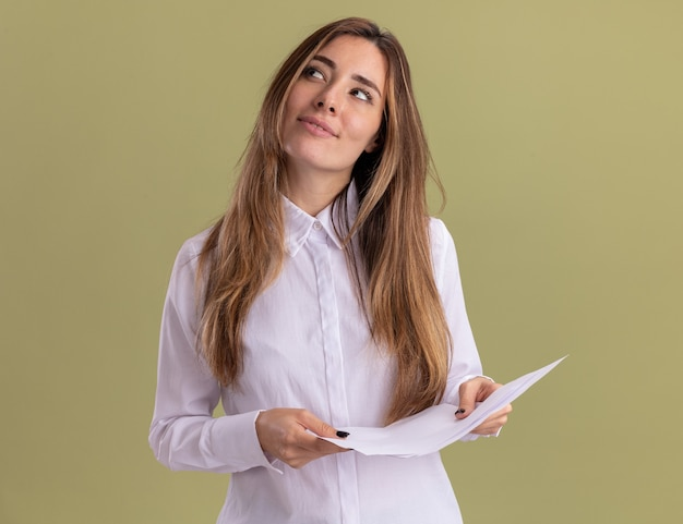 Zadowolona młoda ładna kaukaska dziewczyna trzyma puste kartki papieru i patrzy na bok na białym tle na oliwkowej ścianie z miejsca na kopię