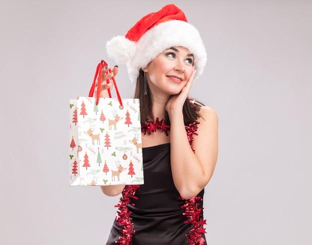 Zadowolona młoda ładna kaukaska dziewczyna ubrana w santa hat i blichtr wianek wokół szyi trzymająca świąteczną torbę prezentową trzymając rękę na twarzy patrząc na bok na białym tle z miejsca kopiowania