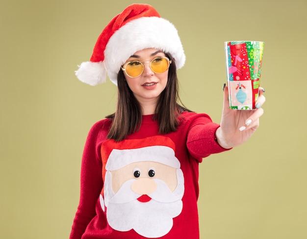 Zadowolona młoda ładna kaukaska dziewczyna ubrana w sweter świętego mikołaja i kapelusz w okularach, wyciągając plastikowy kubek świąteczny w kierunku kamery, patrząc na to na białym tle na oliwkowo-zielonym tle