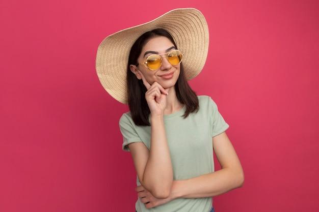 Zadowolona młoda ładna kaukaska dziewczyna w kapeluszu plażowym i okularach przeciwsłonecznych, kładąca rękę na brodzie odizolowana na różowej ścianie z miejscem na kopię