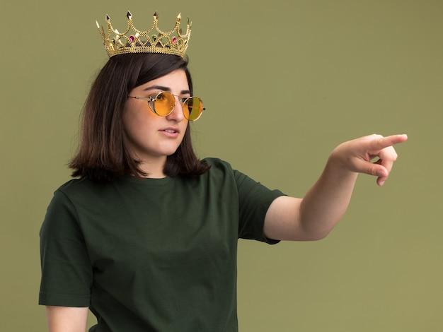 Zadowolona młoda ładna kaukaska dziewczyna w okularach przeciwsłonecznych z koroną patrzącą i wskazującą na bok