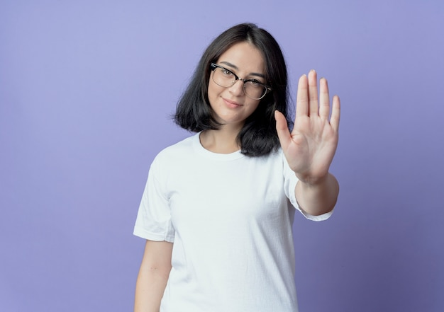 Zadowolona młoda ładna kaukaska dziewczyna w okularach, wskazując stop na aparat na białym tle na fioletowym tle z miejsca na kopię