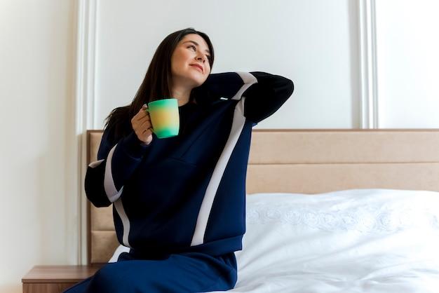 Zadowolona młoda ładna kaukaska kobieta siedzi na łóżku w sypialni trzymając kubek, patrząc na bok, kładąc rękę za szyją