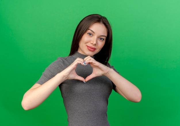 Zadowolona młoda ładna kobieta robi znak serca na białym tle na zielonym tle