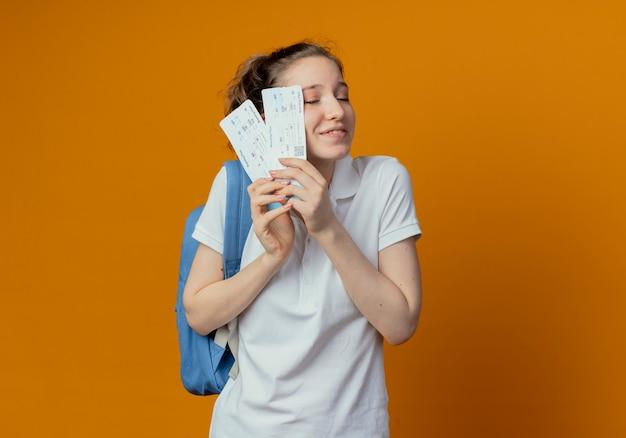 Zadowolona młoda ładna studentka na sobie tylną torbę, trzymając bilety lotnicze z zamkniętymi oczami na białym tle na pomarańczowym tle z miejsca na kopię