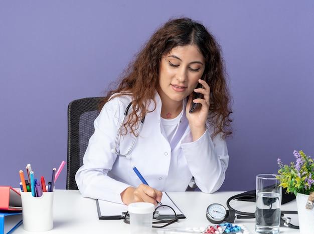 Zadowolona młoda lekarka ubrana w szatę medyczną i stetoskop, siedząca przy stole z narzędziami medycznymi, rozmawiająca przez telefon, patrząc w dół, pisząc receptę w schowku za pomocą pióra
