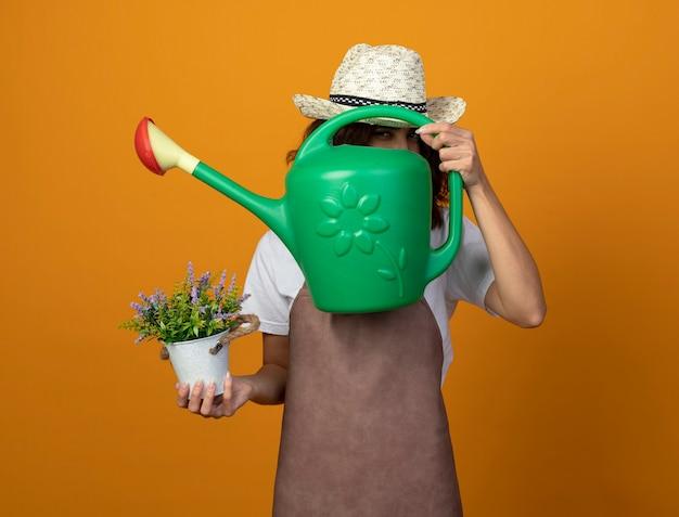 Zadowolona młoda ogrodniczka w mundurze na sobie kapelusz ogrodniczy trzymająca kwiat w doniczce zakryta twarz z konewką