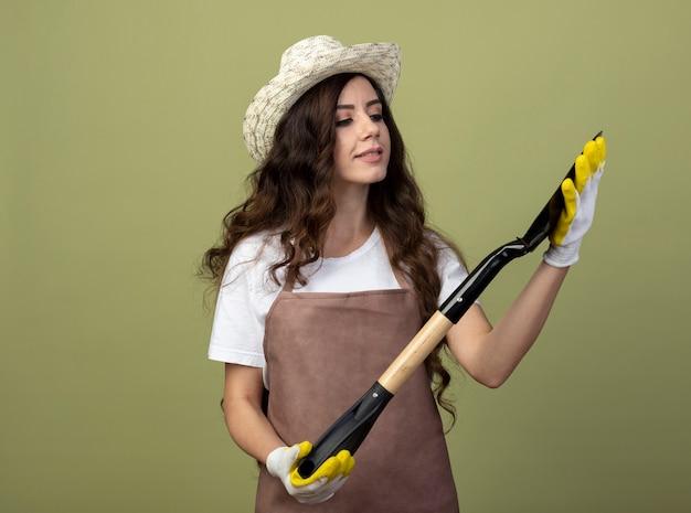 Zadowolona młoda ogrodniczka w mundurze, ubrana w kapelusz ogrodniczy i rękawiczki, trzyma i patrzy na łopatę odizolowaną na oliwkowej ścianie