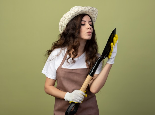 Zadowolona młoda ogrodniczka w mundurze, ubrana w kapelusz ogrodniczy i rękawiczki, udaje, że całuje łopatę na tle oliwkowej ściany