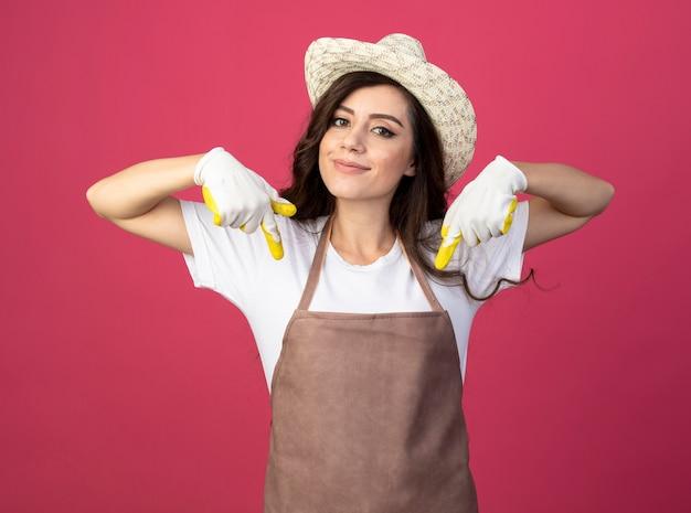 Zadowolona młoda ogrodniczka w mundurze w kapeluszu ogrodniczym i rękawiczkach wskazuje w dół dwiema rękami odizolowanymi na różowej ścianie