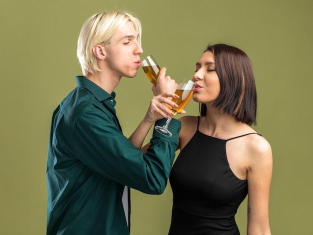 Zadowolona młoda para na walentynki pijąca kieliszek szampana z rękami skrzyżowanymi odizolowana na oliwkowozielonej ścianie