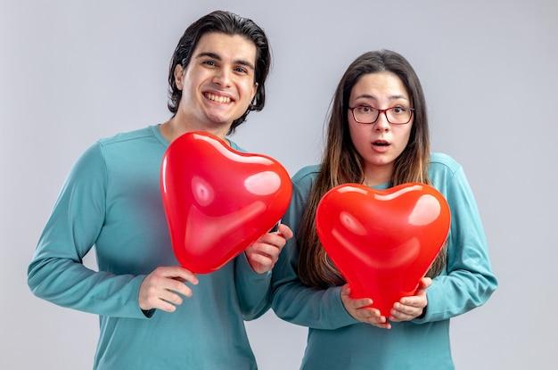 Zadowolona młoda para na walentynki trzymająca balony w kształcie serca na białym tle