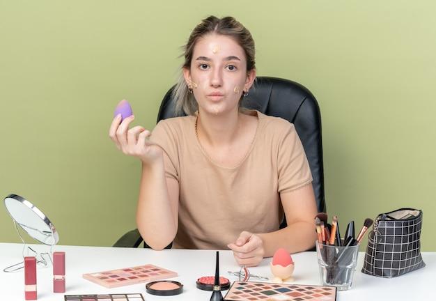 Zadowolona młoda piękna dziewczyna siedzi przy biurku z narzędziami do makijażu z tonizującym kremem na twarzy trzymając gąbkę odizolowaną na oliwkowozielonej ścianie