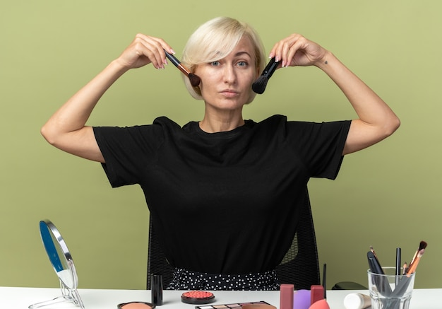 Zadowolona młoda piękna dziewczyna siedzi przy stole z narzędziami do makijażu, nakładając rumieniec w proszku na oliwkowozielonej ścianie