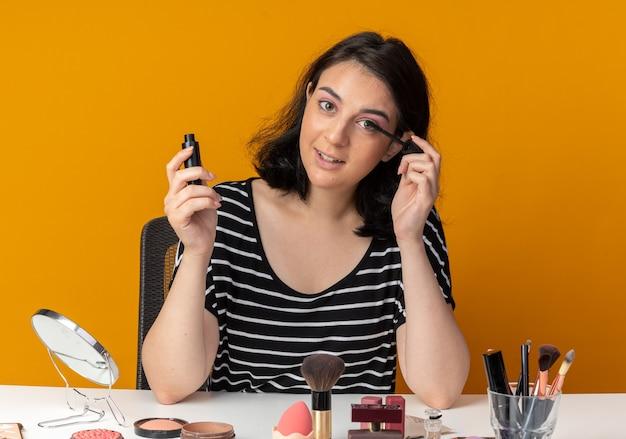 Zadowolona młoda piękna dziewczyna siedzi przy stole z narzędziami do makijażu, nakładającymi tusz do rzęs na pomarańczowej ścianie