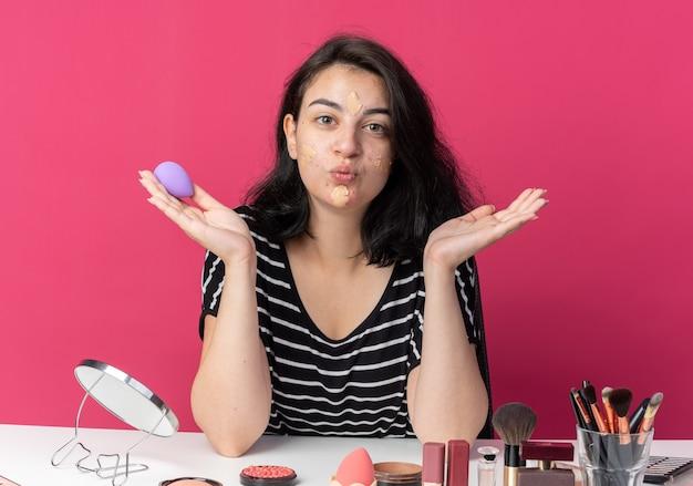 Zadowolona młoda piękna dziewczyna siedzi przy stole z narzędziami do makijażu, stosując krem tonujący, trzymając gąbkę rozprowadzającą ręce pokazujące gest pocałunku na różowej ścianie